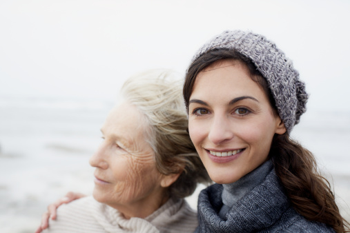 Brunette woman with mother on the beach, portrait