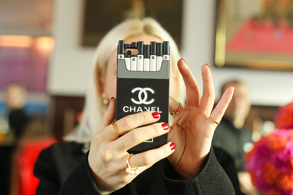 BERLIN, GERMANY - JANUARY 20: A visiter takes a photo by using a smartphone with a Chanel cover during the Thomas Sabo Press Cocktail event on January 20, 2016 in Berlin, Germany. (Photo by Christian Marquardt/Getty Images)