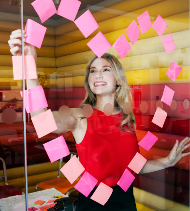 Businesswomen making heart with notes