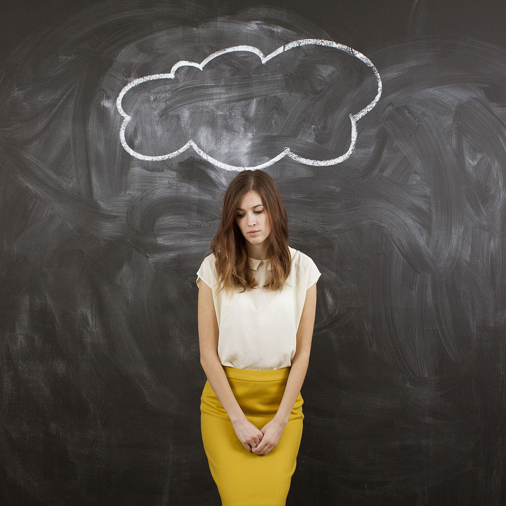 Studio portrait of woman standing under chalk cloud