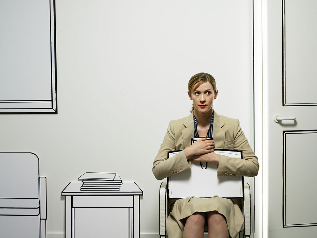 Young business woman sitting in card cut out waiting room